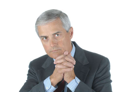 50 yrs: Portrait of a Serious Middle Aged Businessman with hand clasped in front of chin isolated over white Stock Photo