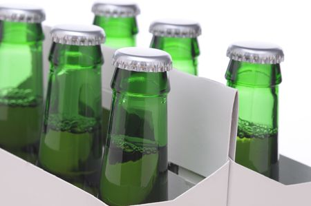6 pack beer: Close up of a Six Pack of Green Beer Bottles in Cardboard Carrier isolated on horizontal format Stock Photo