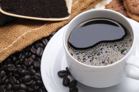 Close up of a delicious fresh hot cup of coffee with with beans grinds and cookies shallow DOF horizontal format photo