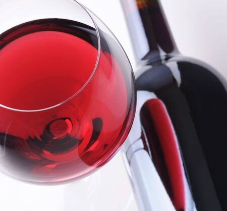 Red Wineglass with Reflection in Bottle laying on its side Stock Photo