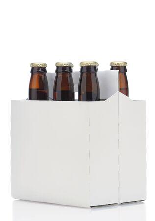 Zes pack bruin bier flessen in lege vervoerder op een hoek van 45 graden geïsoleerd op een witte achtergrond  Stockfoto