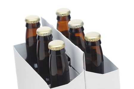 Close up of Six Pack of brown Beer Bottles in Cardboard Carrier isolated on white horizontal shallow depth of field Stock Photo