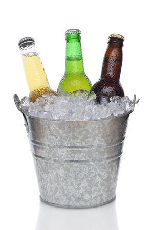 Drie verschillende beer flessen in bucket van ijs met verticale samenstelling condensatie op de witte achtergrond  Stockfoto