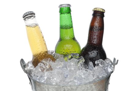 Close up of Three Different Beer Bottles in bucket of ice with condensation horizontal composition over white background photo
