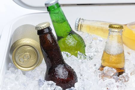 ice chest: Close up of an assortment of beer bottles and cans in cooler with ice horizontal composition Stock Photo