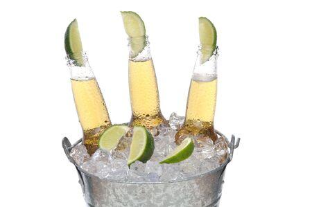 Tres botellas de cerveza borrar con líneas en el cuello en un cubo de hielo aislado en formato horizontal blanco