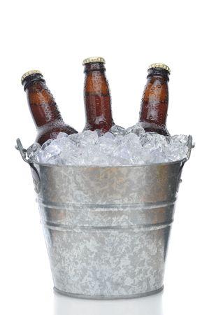 composition vertical: Tre bottiglie di birra Brown nel secchio di ghiaccio con condensa isolato sulla composizione verticale bianco con la riflessione
