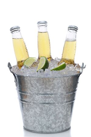 Three Clear Beer Bottles in Ice Bucket with Condensation and limes isolated on white vertical composition with reflection