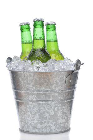 composition vertical: Tre bottiglie di birra verde nel secchio di ghiaccio con condensazione isolato sulla composizione verticale bianco con la riflessione