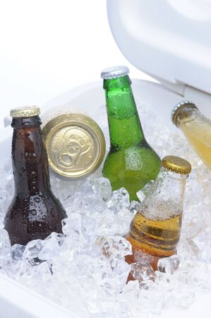 ice chest: Close up of an assortment of beer bottles and cans in cooler with ice vertical composition