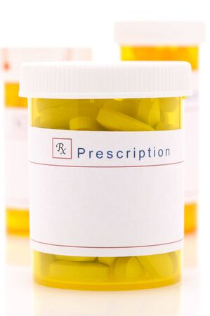 pills bottle: Close up of a Prescription Bottle with two more bottles behind and out of focus over white with reflections Stock Photo