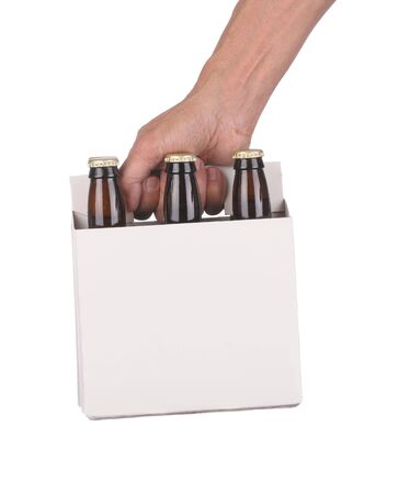 Man's Hand holding a six pack of brown beer bottles isolated over a white background Standard-Bild