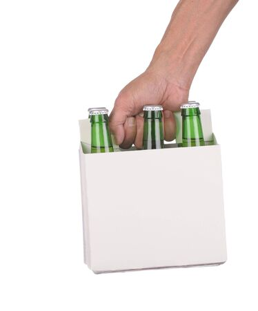 Mans Hand holding a six pack of Green beer bottles isolated over a white background