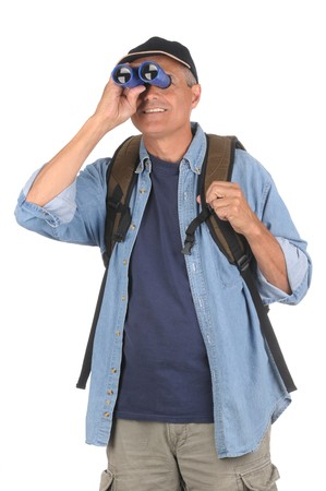 Smiling Middle Aged Man Holding Binoculars up to his eyes. Man is wearing a hat and and unbuttoned outer shirt over a blue t-shirt and carrying a backpack. Shot is a 34 view of the man in vertical format isolated over white. photo