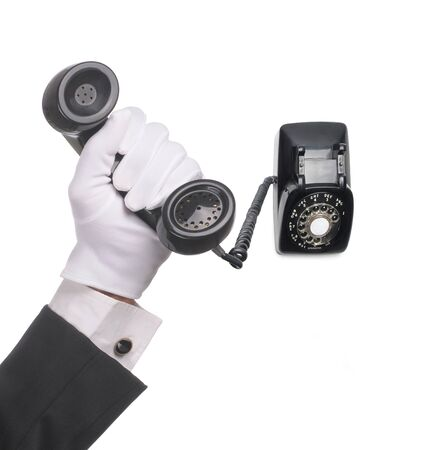 earpiece: Butlers hand holding and antique rotary dial telephone isolated over white background with receiver close to camera and base toward background Square format with hand closer to camera.