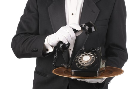 telephone: Butler Holding an Old Rotary Telephone on a tray with the receiver in his other hand isolated on white torso only Stock Photo