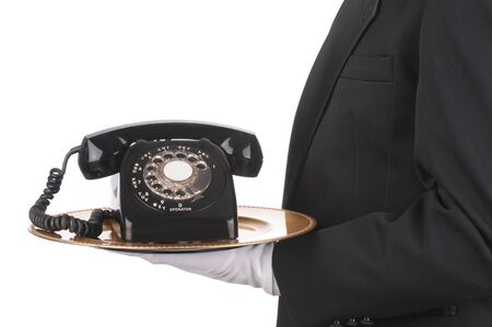 Butler Holding an Old Rotary Telephone on a tray  isolated on white side view of person torso only photo