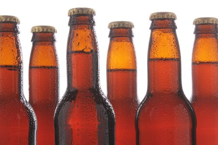 Close up of six brown beer bottles with condensation. Horizontal format over a white background