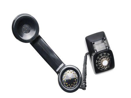 rotary dial telephone: Antiguos Antique Rotary tel�fono aislados sobre fondo blanco con receptor cerca a la c�mara y la base hacia el fondo dispar� con lente de gran angular para acentuar la pieza de o�do de tel�fono ligeramente suave