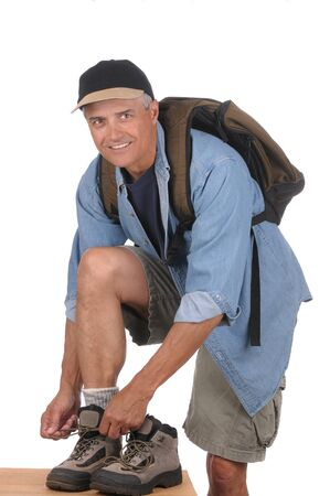 tying: Smiling middle aged man wearing a day pack preparing for a hike. Man is bent over with his foot resting on a wooden surface tying one boot lace. Vertical Format isolated over white .