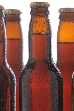 Close up of brown beer bottles with condensation. Vertical format over a white background with selective focus. Stock Photo