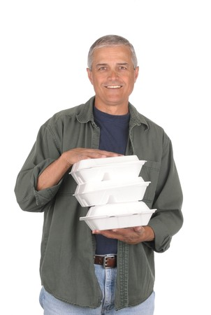 takeout: Smiling middle aged man carrying three take-out food containers. 34 shot of man in vertical format isolated on white.