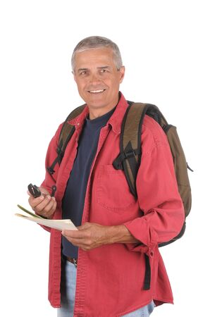 Smiling middle aged man wearing a backpack and holding a map and compass in his hands. 34 view of man shot in vertical format isolated over white . Banco de Imagens