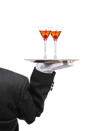 Butler in Tuxedo seen from behind with two Manhattan Cocktails on serving tray held at shoulder height vertical format over white photo