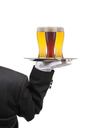 Butler in Tuxedo seen from behind with three beer Glasses on serving tray held at shoulder height vertical format over white photo