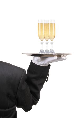 Butler in Tuxedo seen from behind with three champagne glasses on serving ray held at shoulder height vertical format over white photo