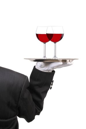 Butler in Tuxedo seen from behind with two red Wine Glasses on Tray held at shoulder height vertical format over white
