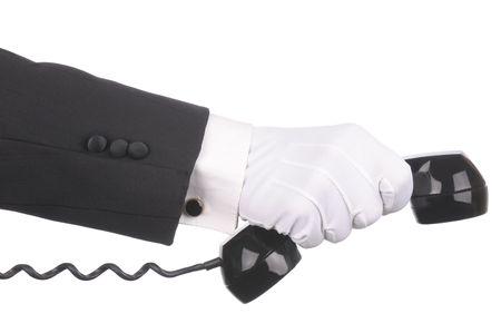 rotary dial telephone: Butler extendidos de receptor de tel�fono de dial rotatorio de celebraci�n y antig�edades en mano aislado sobre fondo blanco. Mano y el brazo s�lo. Foto de archivo