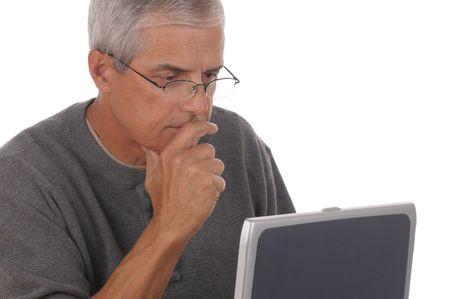 중간의 초상화 그의 랩탑 컴퓨터에서 찾고 있으면 백인 남자 세. 남자는 그의 턱에 그의 손으로 캐주얼 복장을 입고있다. 화이트 절연 가로 형식으로