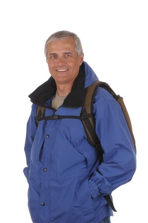 anorak: Middle aged man wearing a blue anorak and backpack isolated over white Stock Photo