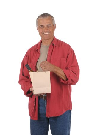 Smiling middle aged man with wine bottle in brown gift bag isolated on white. photo
