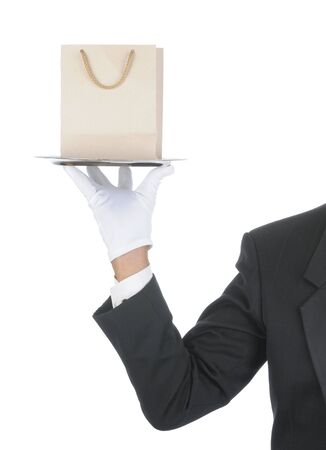 Butler wearing tuxedo and formal gloves holding a Gift Bag on a silver tray. Shoulder hand and arm only isolated on white vertical composition.