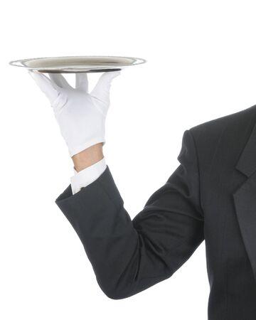Butler vistiendo esmoquin y guantes formales sosteniendo una bandeja de plata. Mano de hombro y el brazo sólo aislados en composición vertical blanco. Foto de archivo