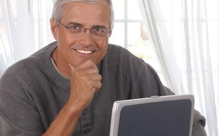 中年男の彼のラップトップ コンピューターとリビング ルームの窓の前に。 写真素材