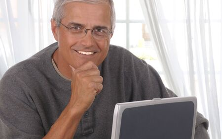 a year older: Middle aged man in front of living room window with his laptop computer. Stock Photo