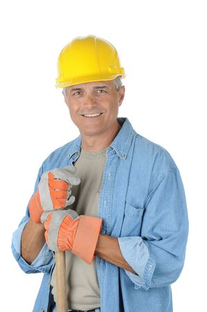 vertical format: Workman holding onto the handle of his shovel. Man is wearing a hard hat and smiling at the camera. Isolated over white in vertical format. Stock Photo
