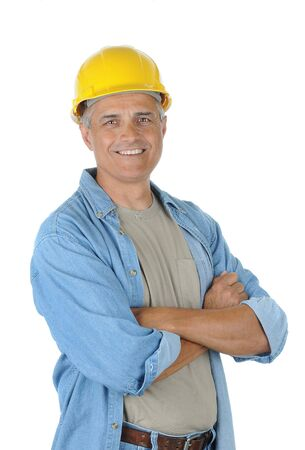 hard: Workman wearing a yellow hard hat and smiling at the camera with his arms crossed. Isolated over white in vertical format. Stock Photo