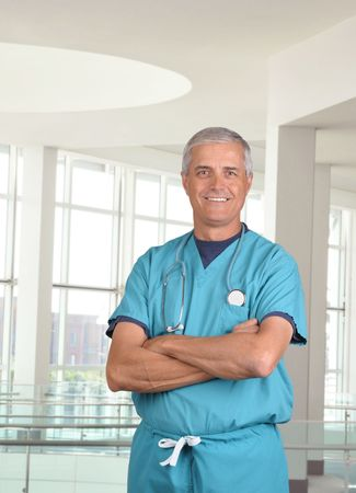 50 yrs: Smiling male doctor in scrubs with a stethoscope around his neck and his arms crossed. Vertical format 34 torso view in modern looking medical facility. Stock Photo