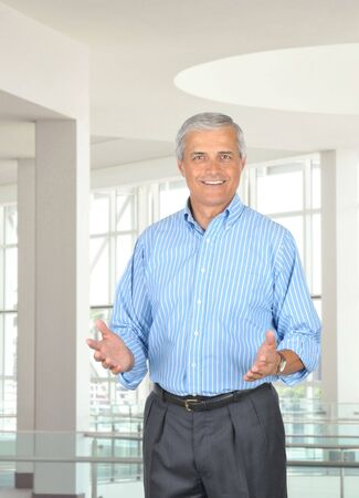 Middle aged businessman in modern office setting gesturing with both hands. Vertical format with 3/4 view of man who is smiling. Stock Photo - 7415435