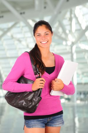 Smiling female teenage student with long brown hair holding a laptop computer and her purse. Brunette girl wearing shorts in vertical format inside modern building. photo
