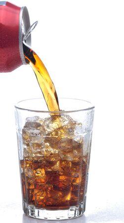 frisdrank: Gieten van een blikje in een glas cola gevuld met ijs. Over witte achtergrond met waterdruppels op de tabel oppervlak. Stockfoto
