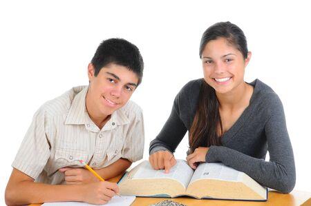 reference book: Dos estudiantes juntos. Adolescente y chica con gran libro de referencia sobre su escritorio. ambos est�n sonriendo a la c�mara. Formato horizontal aislado en blanco.