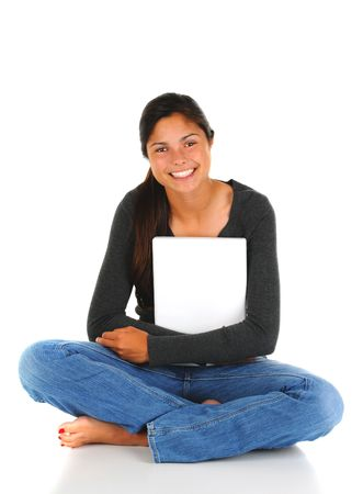 Smiling female teenage student sitting with her legs crossed clutching her closed laptop computer. Vertical format isolated on white. photo
