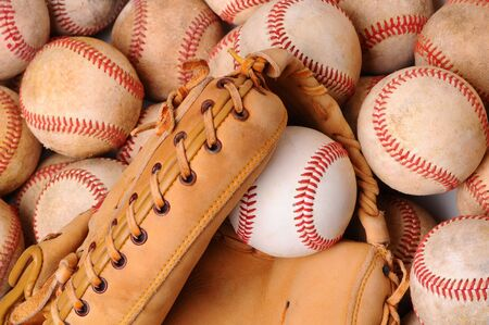 catchers mitt: A pile of used baseballs with a catchers mitt and new laying on top. Horizontal Format.