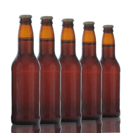 Five Brown Beer Bottles with condensation and reflections isolated on white