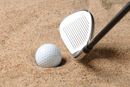 wedges: Golf Ball in Trap with Sand Wedge about to strike the Golfball. Close up in horizontal composition with copy space.